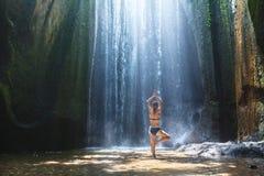 A ioga, mulher bonita pratica na harmonia da cachoeira, do corpo e da mente fotos de stock