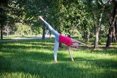 Ioga no parque, fora, saúde do ` s das mulheres, mulher da ioga O conceito do estilo de vida e da recreação saudáveis jovens flex Foto de Stock