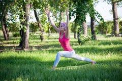 Ioga no parque, fora, saúde do ` s das mulheres, mulher da ioga O conceito do estilo de vida e da recreação saudáveis jovens flex Fotos de Stock