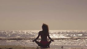 A ioga practic da menina na praia no por do sol Moça que faz o exercício em uma praia tropical Silhueta de uma ioga da mulher vídeos de arquivo