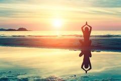 Ioga praticando da jovem mulher da silhueta na praia imagens de stock