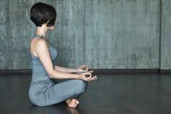 Ioga praticando da jovem mulher em um fundo do muro de cimento cinzento Fotos de Stock