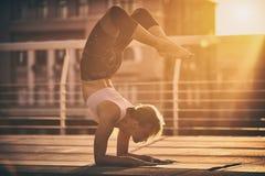 Ioga praticando da jovem mulher, estando na pose do escorpião de Vrischikasana no terraço no por do sol Foto de Stock