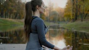 Ioga praticando da jovem mulher fora A fêmea medita exterior na frente da natureza bonita do outono