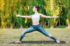 Ioga praticando da jovem mulher magro na natureza Pose de Virabhadrasana imagens de stock royalty free