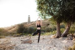 Ioga praticando da jovem mulher na praia pelo por do sol imagens de stock