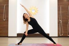 Ioga praticando da jovem mulher no gym brilhante Estilo de vida de Streching e de bem-estar fotografia de stock