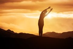 Ioga praticando da jovem mulher no por do sol Imagem de Stock