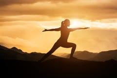 Ioga praticando da jovem mulher no por do sol Imagem de Stock Royalty Free