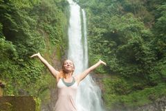 Ioga praticando da jovem mulher pela cachoeira Imagens de Stock Royalty Free