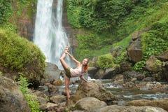 Ioga praticando da jovem mulher pela cachoeira Imagem de Stock