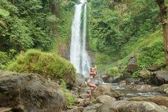 Ioga praticando da jovem mulher pela cachoeira Foto de Stock