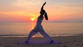 Ioga praticando da mulher asiática no mar do por do sol filme