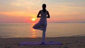 Ioga praticando da mulher asiática no mar do por do sol vídeos de arquivo