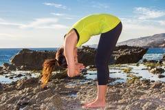 Ioga praticando da mulher asiática saudável na praia que veste a parte superior amarela Fotografia de Stock Royalty Free