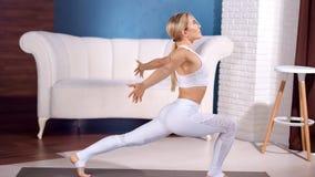 Ioga praticando da mulher bonita atlética em casa que aprecia o estilo de vida saudável em casa video estoque