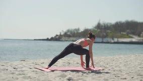 Ioga praticando da mulher bonita nova na praia no dia ensolarado Conceito ativo saudável do estilo de vida filme