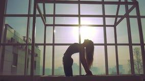 Ioga praticando da mulher contra o fundo da janela em um dia ensolarado video estoque