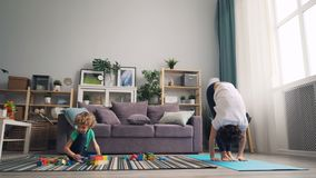 Ioga praticando da mulher flexível em casa quando seu filho novo que joga com blocos vídeos de arquivo