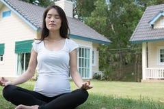 ioga praticando da mulher gravida asiática ao sentar-se no posi dos lótus Imagens de Stock