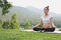 ioga praticando da mulher gravida asiática ao sentar-se no posi dos lótus Fotos de Stock