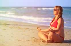 Ioga praticando da mulher gravida na praia imagem de stock royalty free