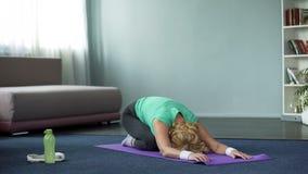 A ioga praticando da mulher madura atlética levanta a casa, a aptidão e a saúde, esticando fotos de stock royalty free