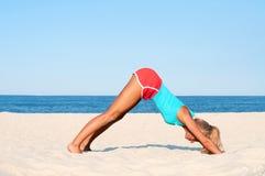 Ioga praticando da mulher na praia foto de stock