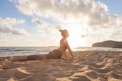 Ioga praticando da mulher na praia do mar no por do sol Fotos de Stock