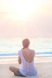 Ioga praticando da mulher na praia do nascer do sol Imagens de Stock
