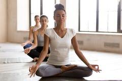 Ioga praticando da mulher negra e do grupo do iogue, fazendo Ardha Padmasan fotos de stock royalty free