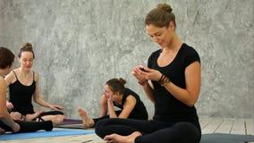 Ioga praticando da mulher no health club Moças que falam e que relaxam após a aptidão, instrutor da ioga que texting no imagens de stock