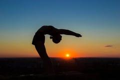Ioga praticando da mulher no por do sol - deixe cair para trás, pose da roda fotografia de stock royalty free