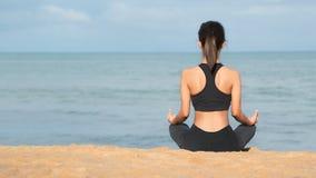 Ioga praticando da mulher nova na praia no por do sol Meditação, ioga praticando da mulher saudável nova na praia no nascer do so foto de stock