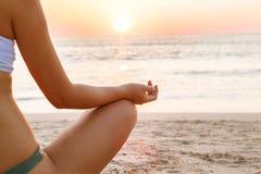 Ioga praticando da mulher pelo mar no por do sol fotografia de stock