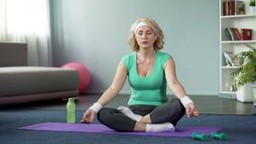 A ioga praticando da senhora madura em casa, fazendo o abrandamento exercita, meditação imagens de stock