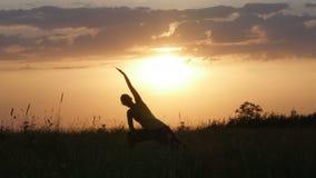 Ioga praticando da silhueta da jovem mulher na frente do por do sol bonito do verão, gora de Fruska, Novi Sad, Sérvia video estoque