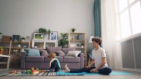 Ioga praticando de amor da mamã que olha seu filho jogar com tijolos e fala video estoque