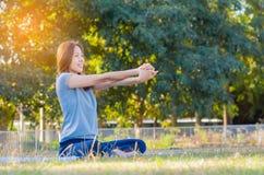 Ioga praticando de sorriso asiática nova da mulher, sentando-se na pose fácil Imagem de Stock
