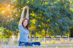 Ioga praticando de sorriso asiática nova da mulher, sentando-se na pose fácil Imagens de Stock Royalty Free