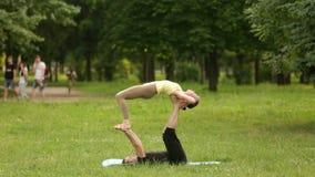 Ioga praticando do acro dos pares bonitos Os instrutores novos da ioga praticam em um parque da cidade na grama verde Dois bem su filme