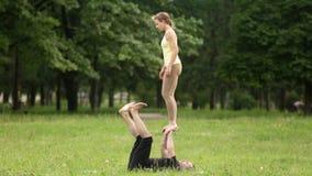 Ioga praticando do acro dos pares bonitos Os instrutores novos da ioga praticam em um parque da cidade na grama verde Dois bem su video estoque