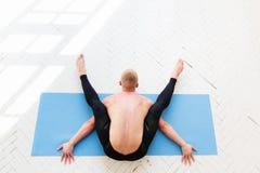 Ioga praticando do homem desportivo Kurmasana Pose da tartaruga Postura da tartaruga Foto de Stock Royalty Free