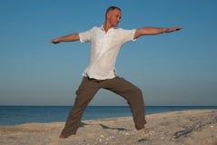 Ioga praticando do homem na costa Imagens de Stock Royalty Free