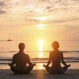 Ioga praticando dos pares novos na praia do mar durante o por do sol Amor Fotografia de Stock Royalty Free