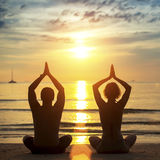 Ioga praticando dos pares novos na praia durante o por do sol Imagem de Stock