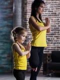 Ioga praticando vestindo da roupa dos esportes da mãe e da filha que medita junto estar em um pé com mãos na oração fotos de stock