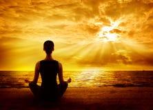 Ioga que medita o nascer do sol, meditação do Mindfulness da mulher na praia Fotografia de Stock