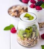 Iogurte branco com o muesli na bacia de vidro com partes de quivi em partes superiores e inteiras no lado direito Fotografia de Stock