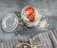 Iogurte branco delicioso em um vidro com bolas, farinha de aveia e fruto do chocolate foto de stock